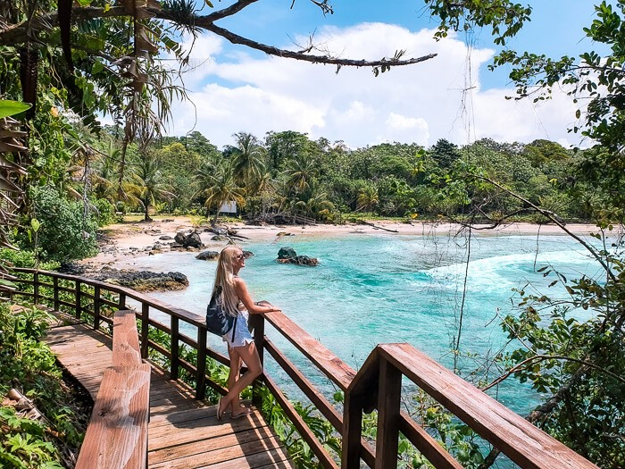 A girl standing on a wooden walkway, enjoying a view over Red Frog Beach, one of the best beaches in Bocas del Toro.