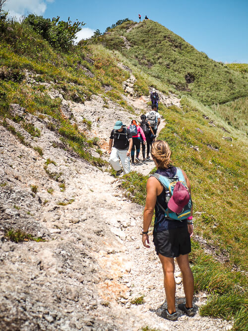 a group of hikers walking on a narrow trail among steep green hills in Panama