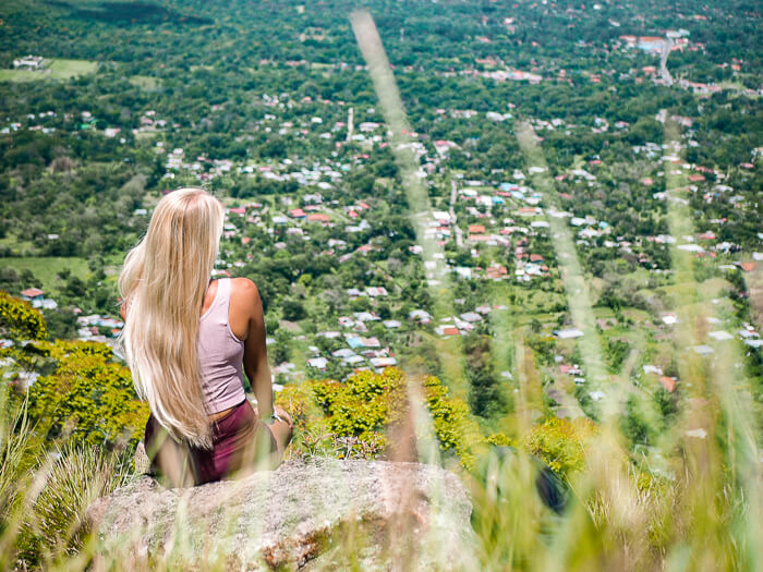 A woman sitting on a rock and enjoying the view of El Valle de Anton, one of the best hiking destinations in Panama