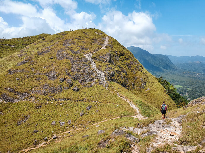 Steep grass-covered hills and a narrow trail of the La India Dormida hike, one of the best things to do in El Valle de Anton