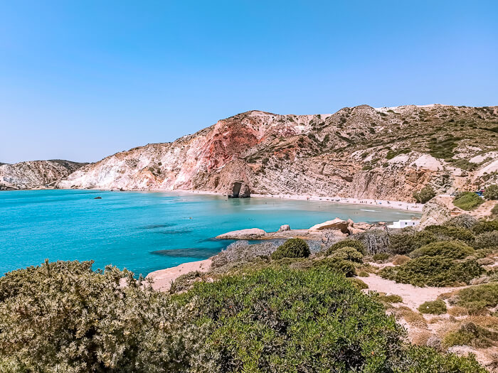 Colorful cliffs and turquoise waters at Firiplaka beach - one of the most popular beaches in Milos