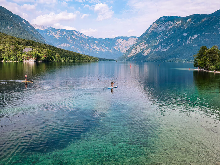 a paddle boarder on the blue green glacial Lake Bohinj surrounded by Julian Alps