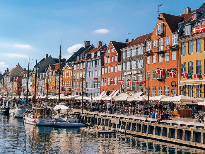 Colorful Nyhavn canal lined with restaurants, old sailboats and historical houses in Copenhagen, Denmark.