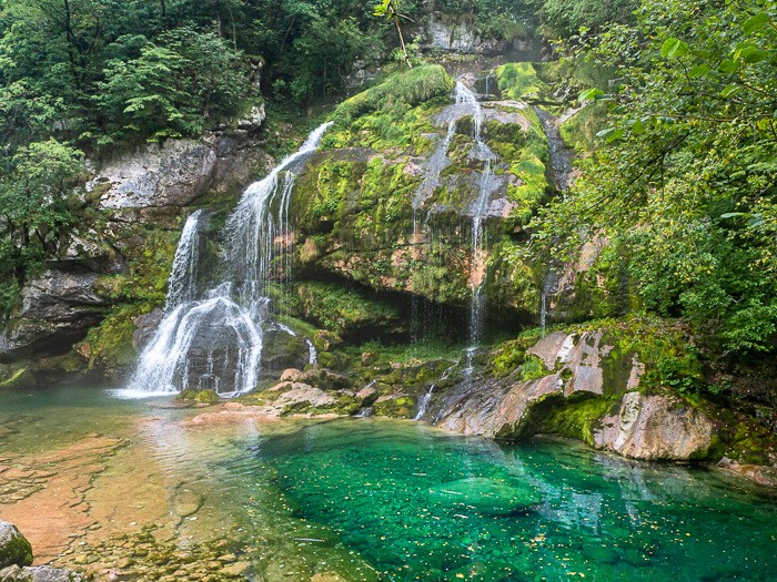An emerald pool and lush vegetation surrounding the small but beautiful Slap Virje Waterfall near the town of Bovec