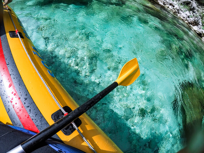 Rafting along a beautiful turquoise river in Slovenia, the perfect outdoor activity for families visiting Bovec.