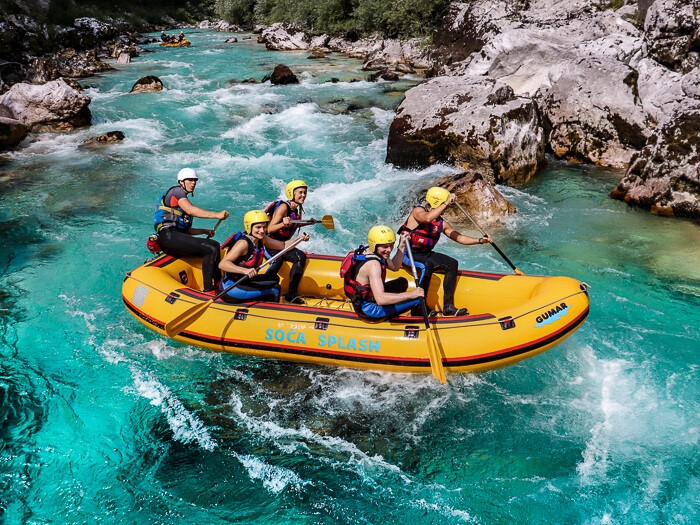 A group of people sitting in a boat rafting on the Soca River, one of the best things to do in Slovenia