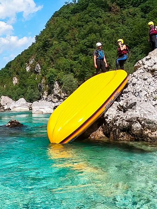 People sliding down a raft on a rafting tour in Slovenia