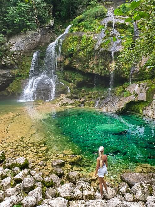 a woman standing on rocks in front of a blue-green basin and Virje Waterfall, one of the best waterfalls in Slovenia