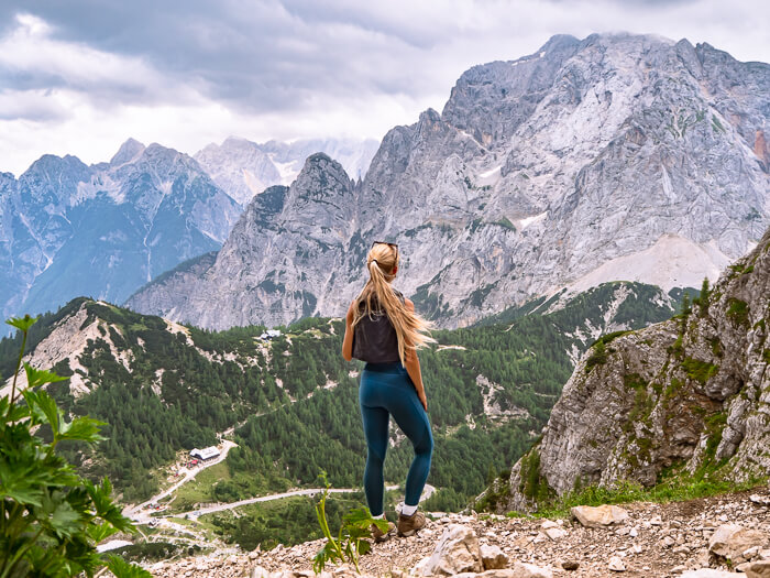 a woman hiking in the Julian Alps and looking at the Vrsic Pass from Mala Mojstrovka hiking trail