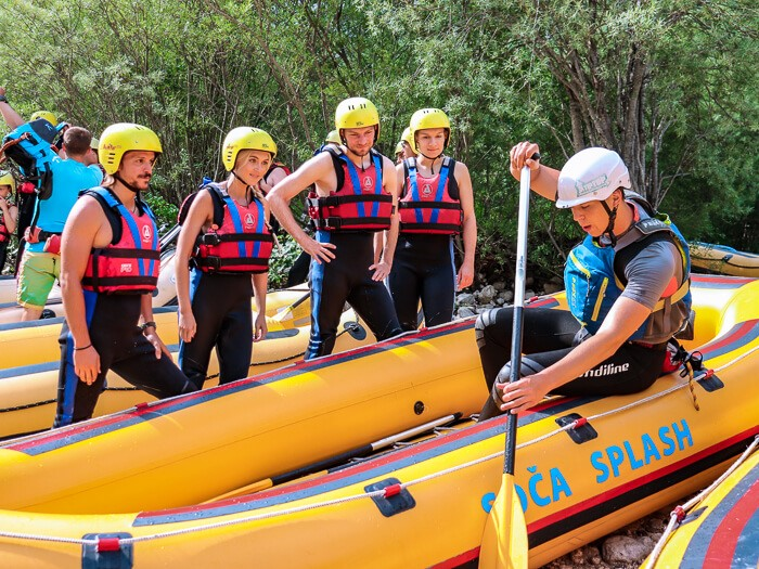 A group of people standing next to a yellow raft and observing the rafting instructor