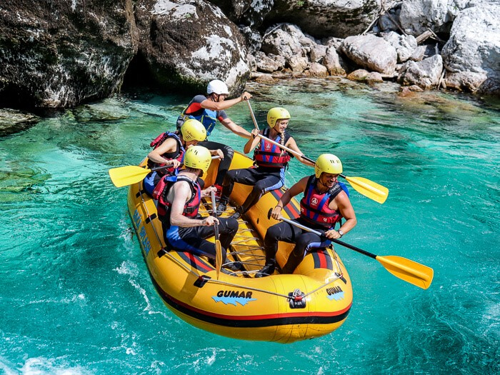 A group of people sitting in an inflatable raft, wearing life jackets and helmets on the Soca River, the best river for rafting in Slovenia
