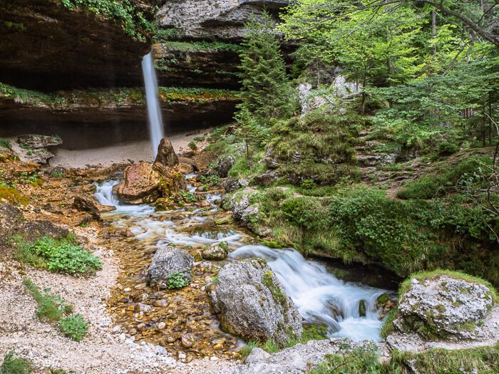 the small upper Peričnik waterfall surrounded by green vegetation and limestone rocks