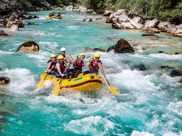 People sitting in a raft and paddling through the frothy rapids of Soca River, the best place for white water rafting in Slovenia