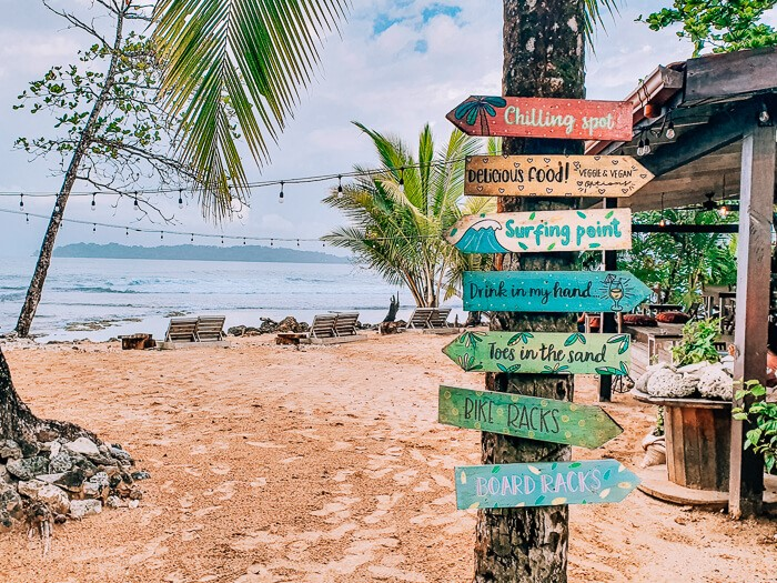 A beach club with sunbeds and colorful signs at Paunch Beach, one of the best surf spots in Bocas del Toro, Panama