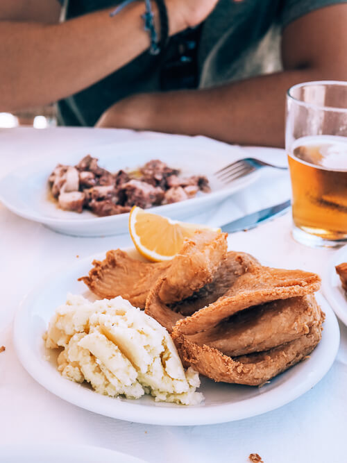 two white plates with Greek seafood dishes