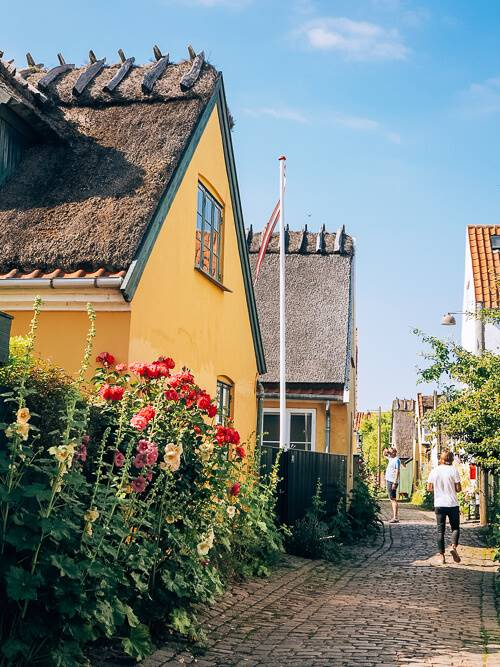 a yellow thatched-roof cottage in the historical town of Dragor in Denmark