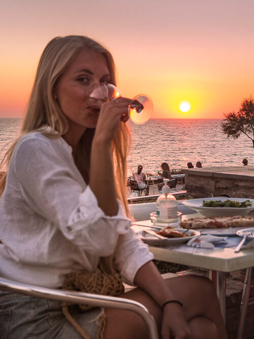 a woman sipping wine at a restaurant and enjoying a sunset