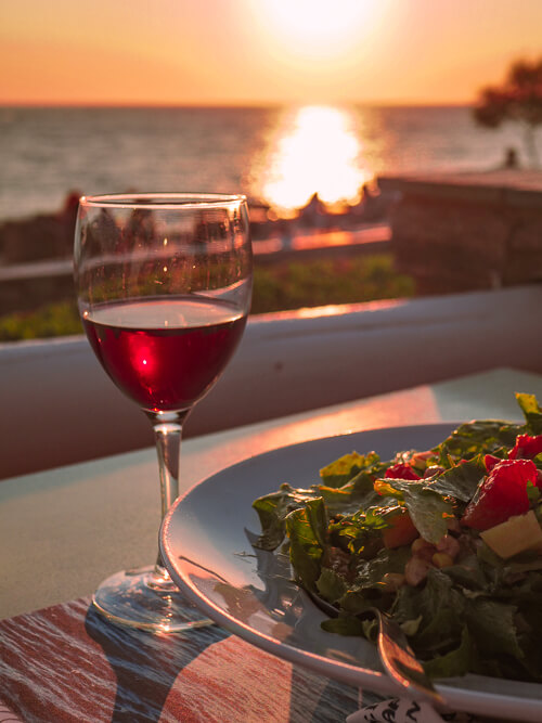 a salad and a glass of red wine with a backdrop of a sunset at a restaurant in Antiparos Island
